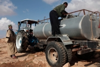 Isma'il transporting water tanks with his tractor. In recent drought years more and more residents are forced to buy expensive water. Simre, November 2011. Photo: Tomer Appelbaum