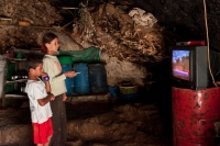 Youssef and his sister watching television in their cave. Tuba, July 2012. Photo: Tomer Appelbaum